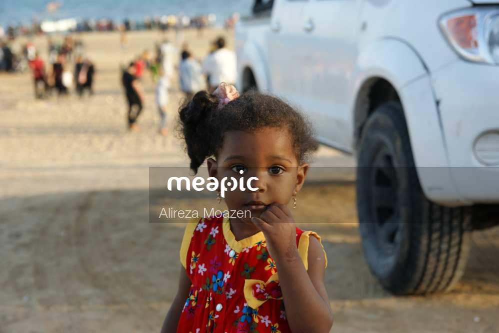 Little Girl Standing In A Parking Lot Stock Photo · Meapic