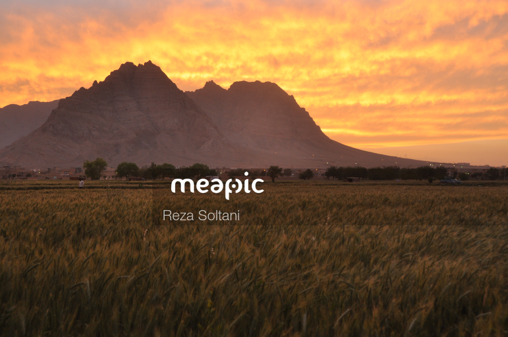 Sunset Over A Grass Field With A Mountain In The Background Stock Photo · Meapic