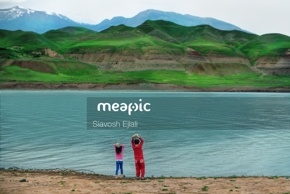 Group Of People On A Beach With A Mountain In The Background Stock Photo · Meapic