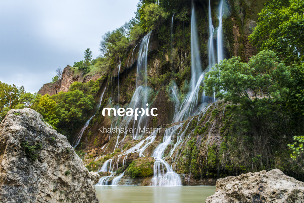 Large Waterfall Next To A Rock Stock Photo · Meapic