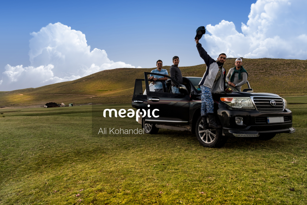 Group Of People In A Field Next To A Car Stock Photo · Meapic