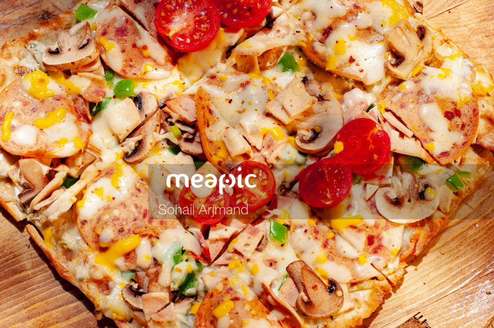 Pizza Sitting On Top Of A Wooden Cutting Board Stock Photo · Meapic