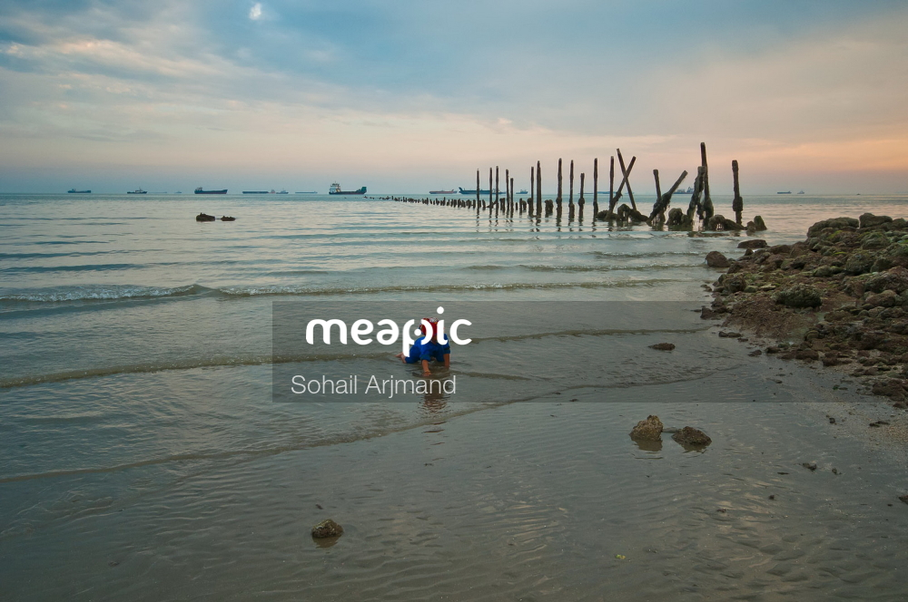 Group Of People On A Beach Near A Body Of Water Stock Photo · Meapic