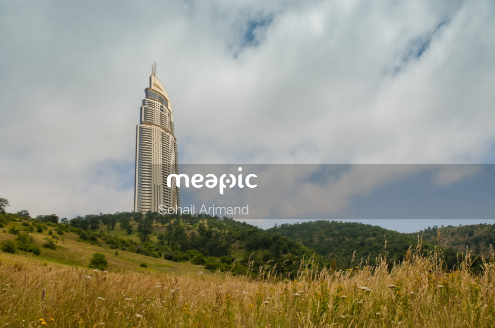 Large Tall Tower With A Clock On Top Of A Lush Green Field Stock Photo · Meapic
