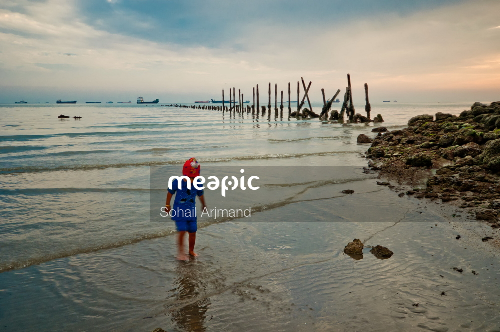 Person Standing On A Beach Near A Body Of Water Stock Photo · Meapic