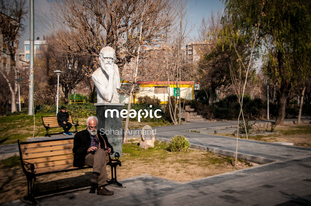 Man Sitting On A Bench In A Park Stock Photo · Meapic