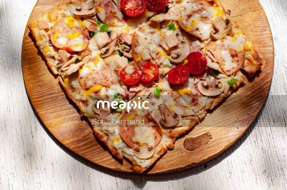 Slice Of Pizza Sitting On Top Of A Wooden Cutting Board Stock Photo · Meapic