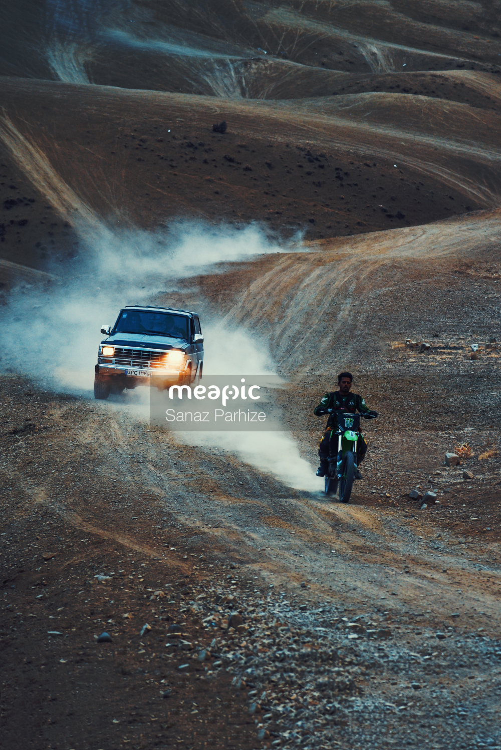 Person Riding On The Back Of A Truck Driving Down A Dirt Road Stock Photo · Meapic