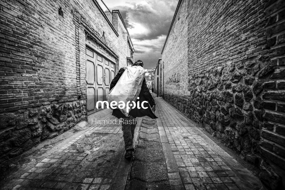 Person Walking Down A Sidewalk Holding An Umbrella Stock Photo · Meapic