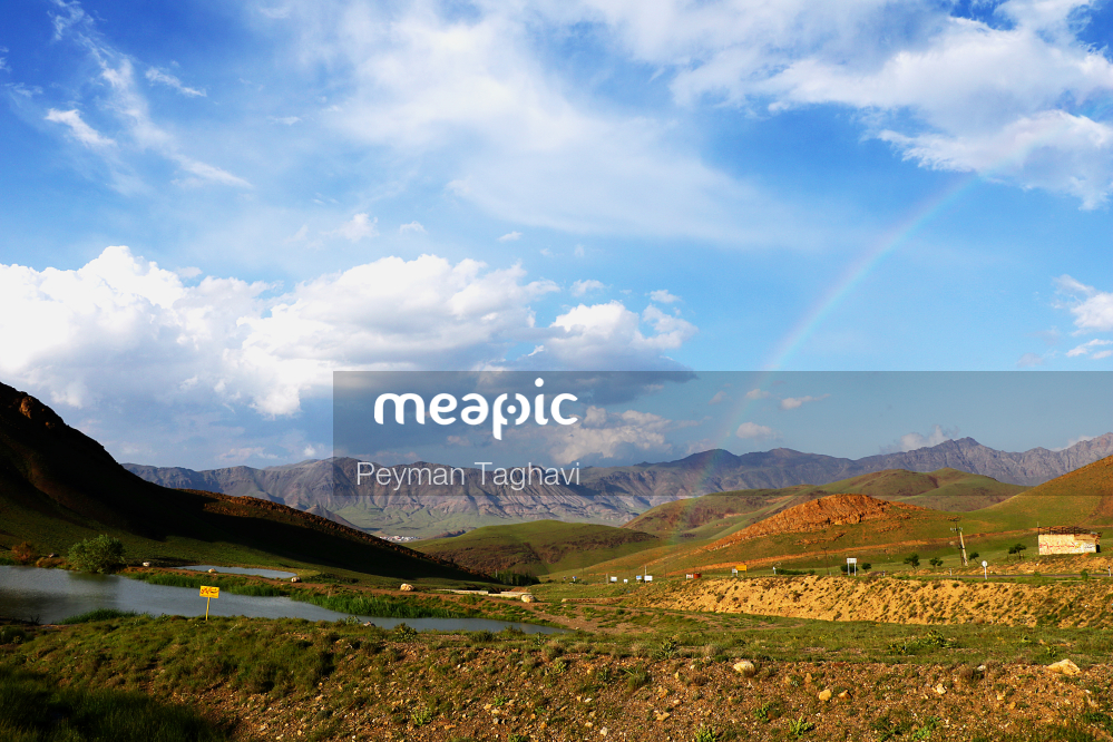 Large Green Field With A Mountain In The Background Stock Photo · Meapic
