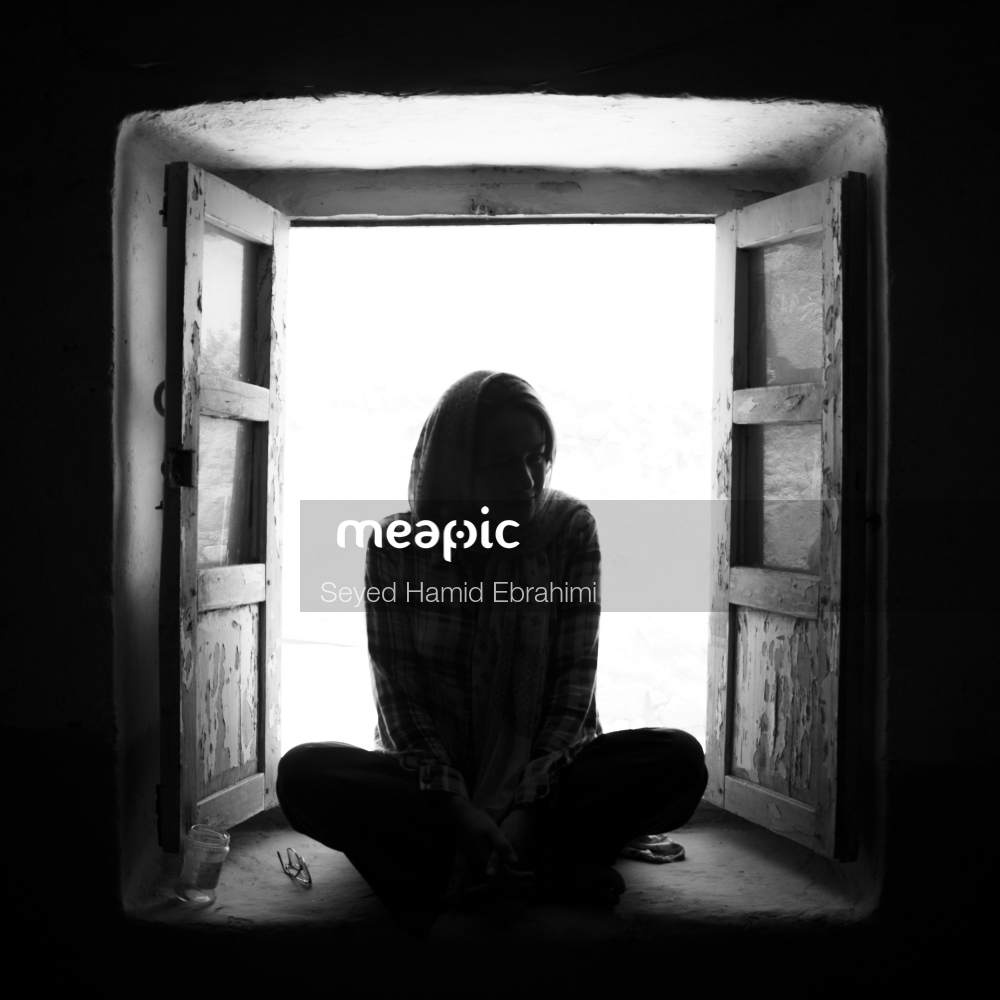 Person Sitting In Front Of A Window Stock Photo · Meapic