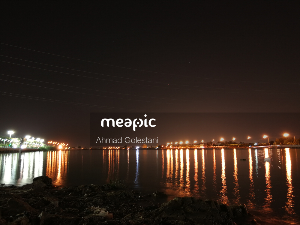 Large Body Of Water With A City In The Night Sky Stock Photo · Meapic