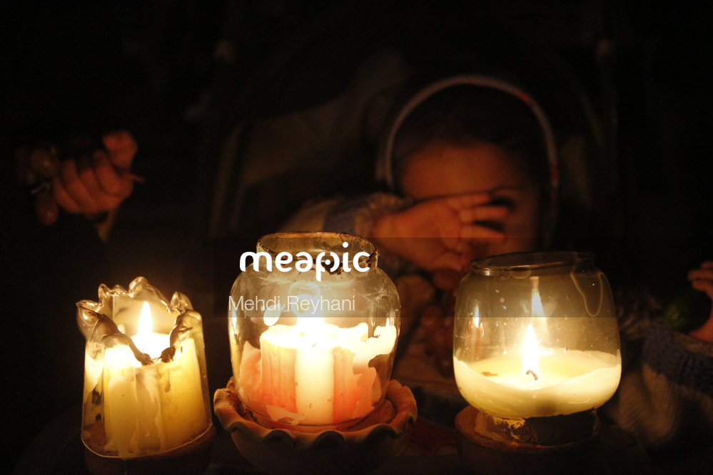 Person Sitting At A Table With Lit Candles Stock Photo · Meapic