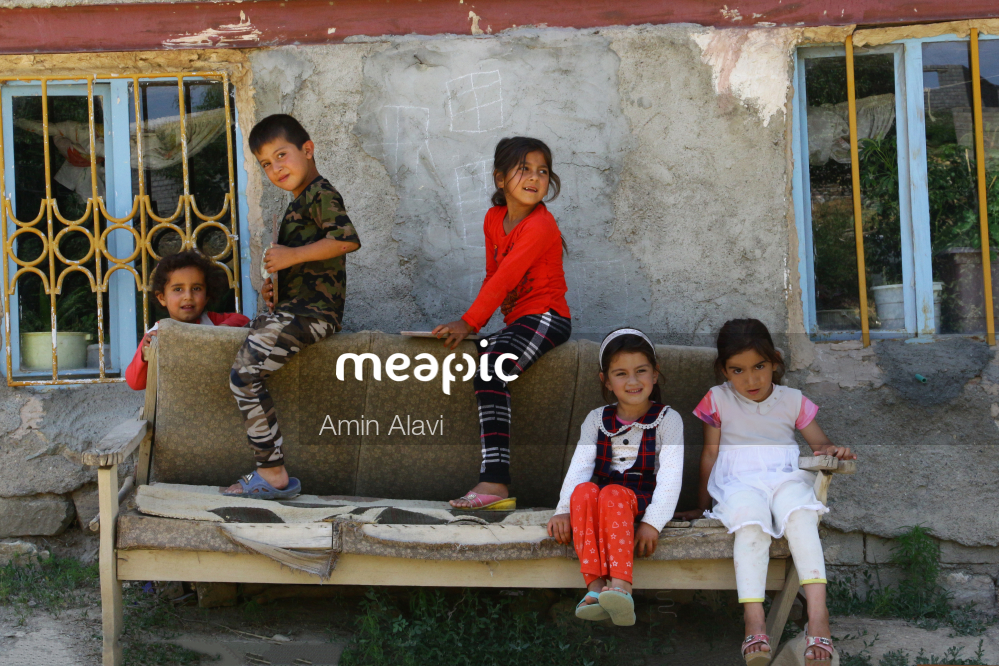 Group Of Young Children Sitting Next To A Building Stock Photo · Meapic