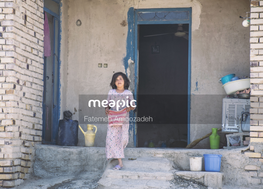 Woman Standing In Front Of A Brick Building Stock Photo · Meapic