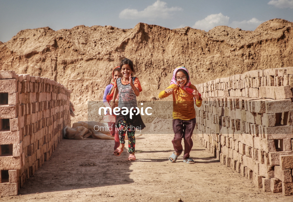 Group Of People Standing In Front Of A Brick Wall Stock Photo · Meapic