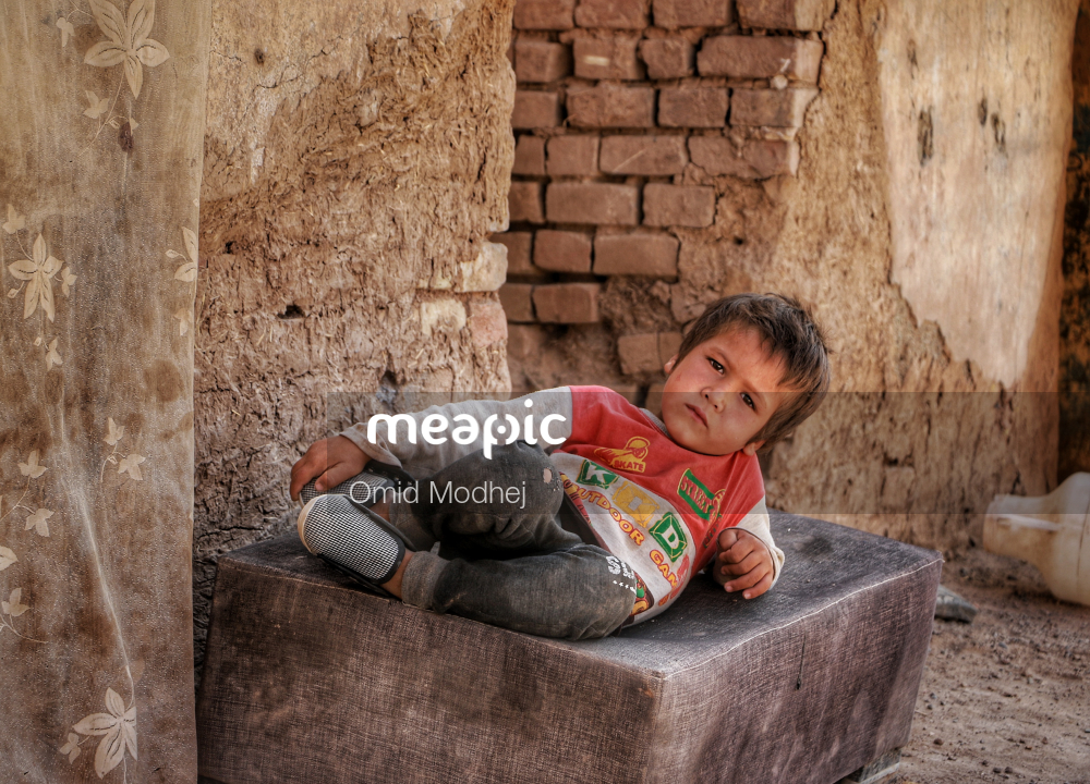 Boy Sitting In Front Of A Brick Wall Stock Photo · Meapic