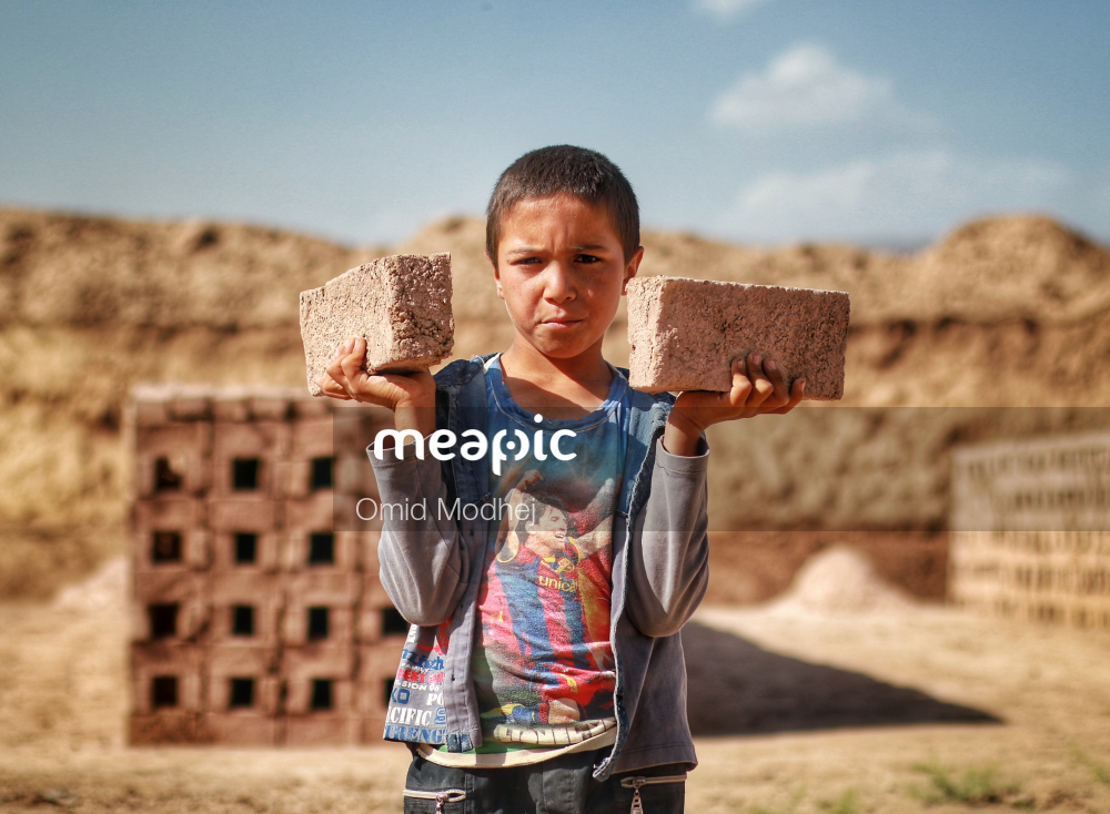 Young Boy Standing In Front Of A Brick Wall Stock Photo · Meapic