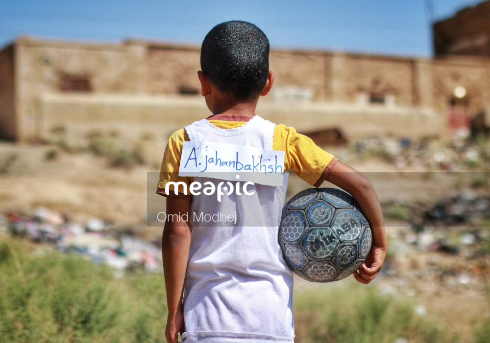 Little Boy That Is Standing In The Grass Stock Photo · Meapic