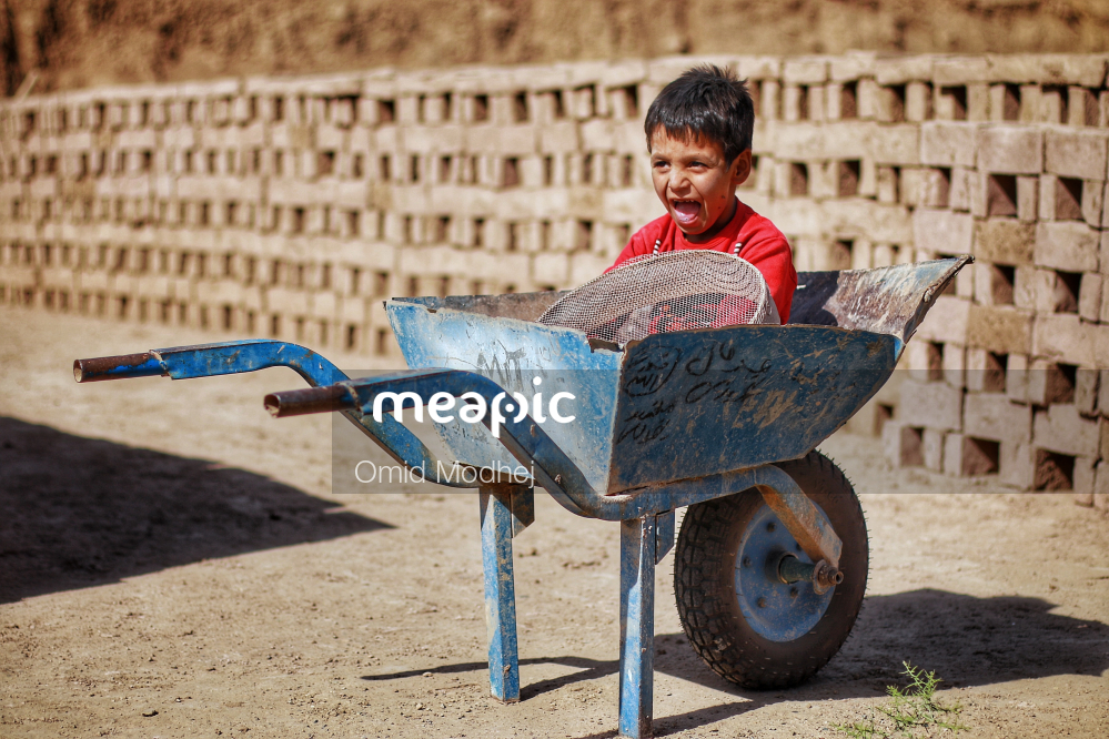 I Am Not Really Confident, But Young Boy Sitting On A Bench Stock Photo · Meapic
