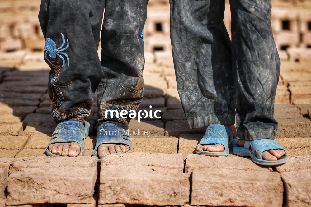 Person Standing Next To A Brick Wall Stock Photo · Meapic