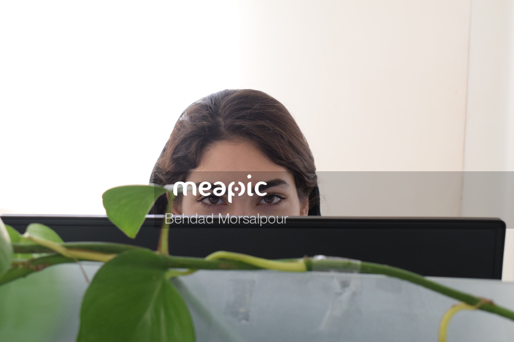 Woman Sitting At A Table In Front Of A Computer Stock Photo · Meapic