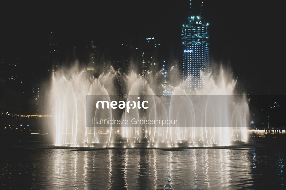 Fountain In Front Of A Body Of Water With The Dubai Fountain In The Background Stock Photo · Meapic