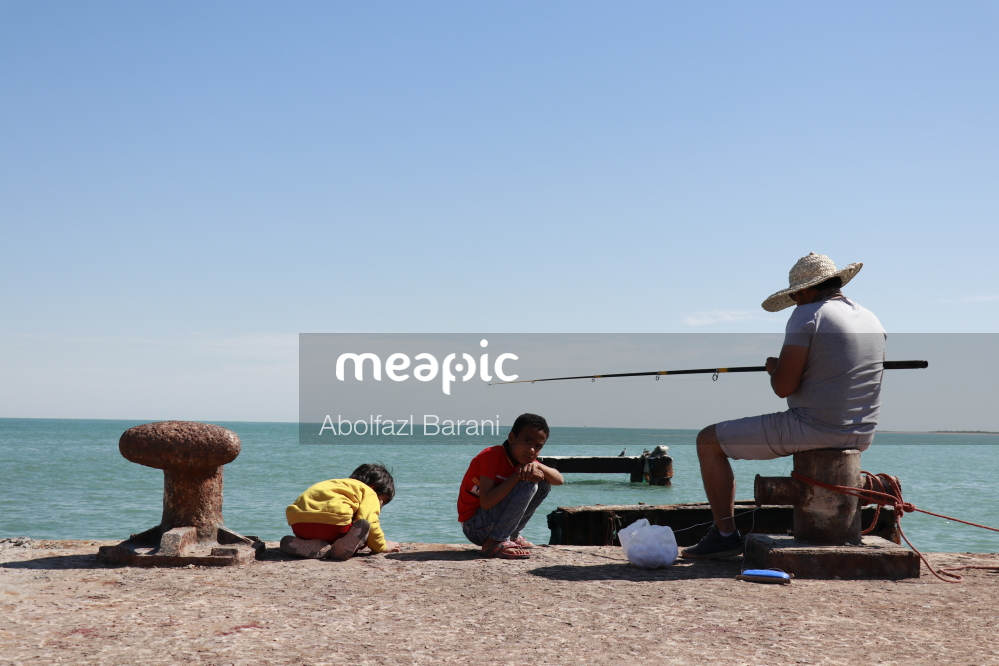 Group Of People Sitting At A Beach Stock Photo · Meapic