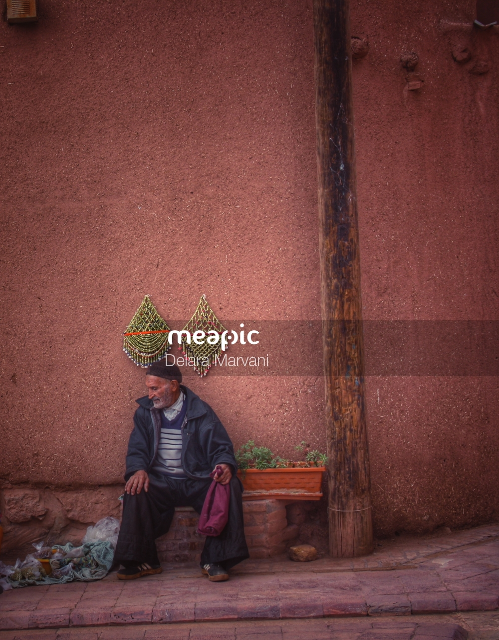 Person Sitting In Front Of A Building Stock Photo · Meapic