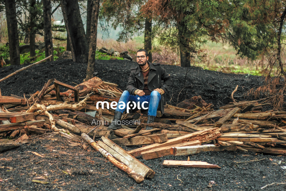 Man Sitting On A Pile Of Wood Stock Photo · Meapic