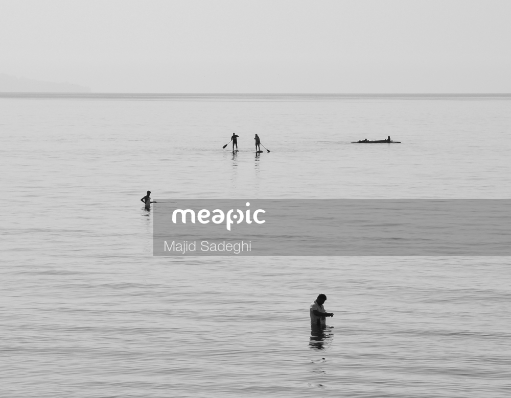 Man Standing Next To A Body Of Water Stock Photo · Meapic