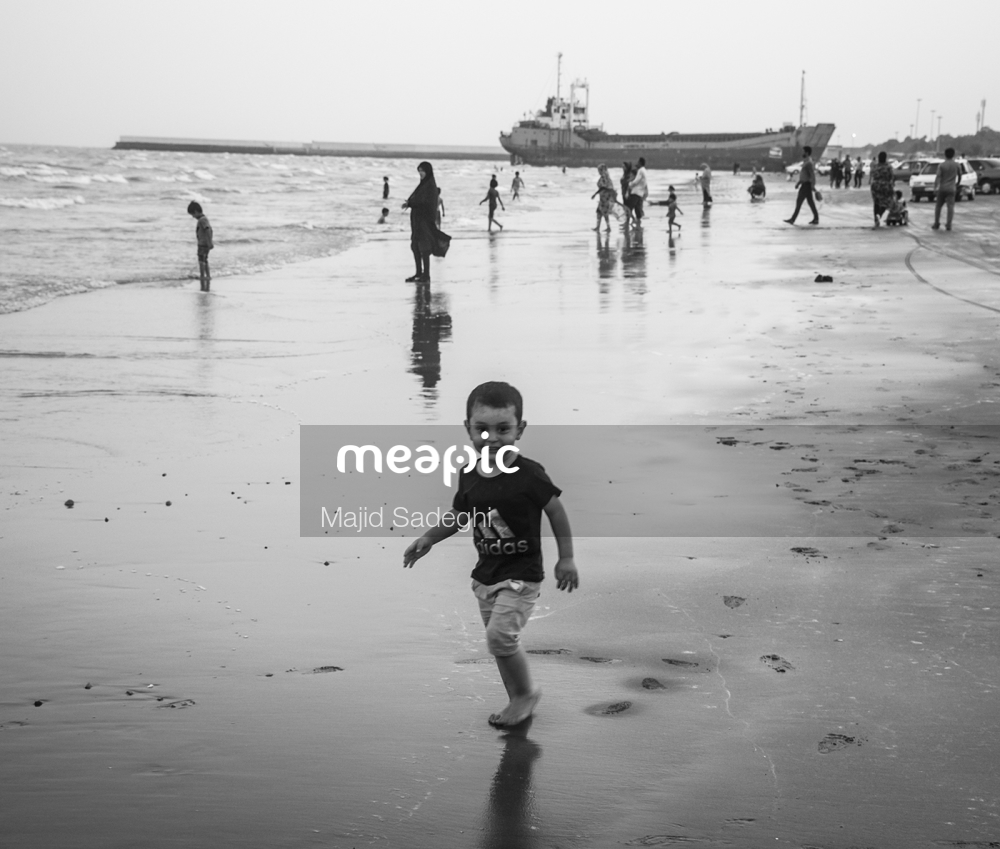 Man Standing On A Beach Near A Body Of Water Stock Photo · Meapic