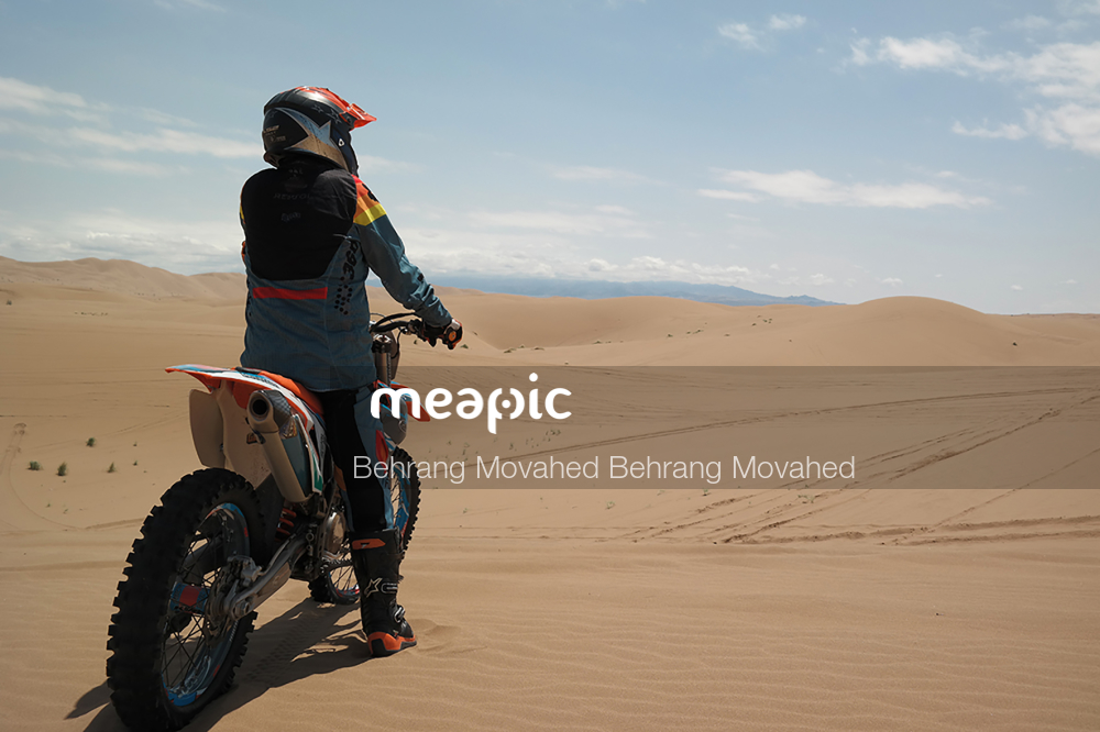Man Riding A Motorcycle Down A Dirt Road Stock Photo · Meapic