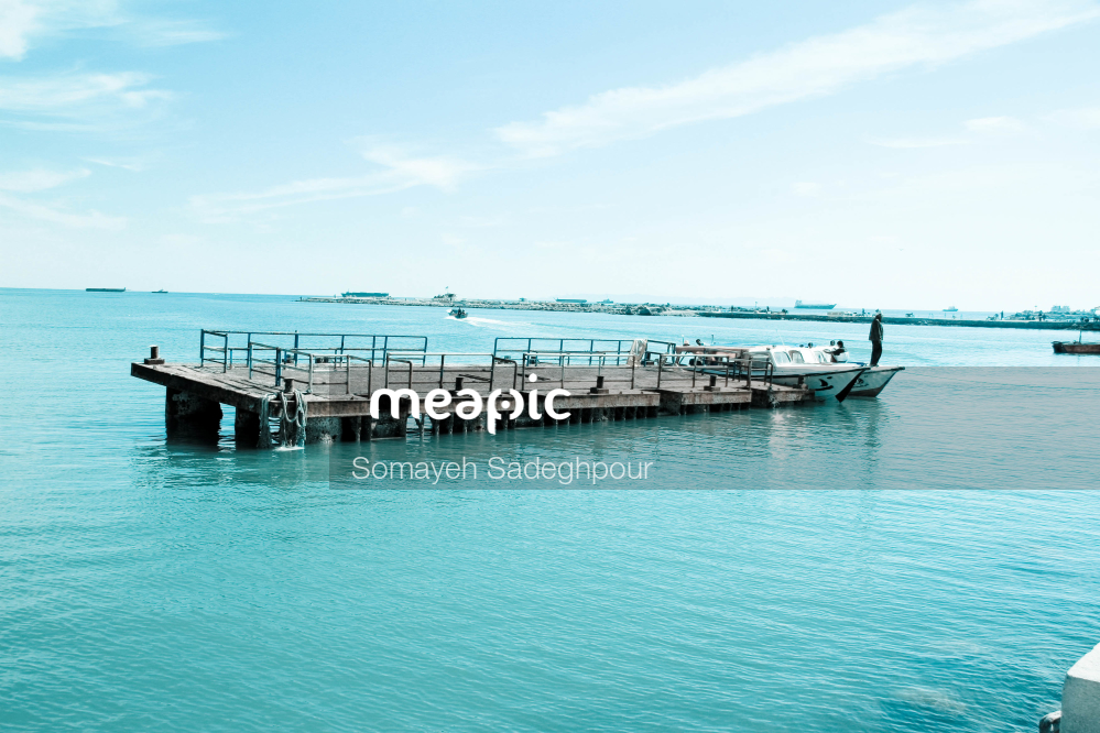 Boat Is Docked Next To A Body Of Water Stock Photo · Meapic
