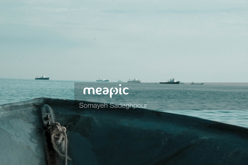 Man Sitting In A Boat On A Body Of Water Stock Photo · Meapic
