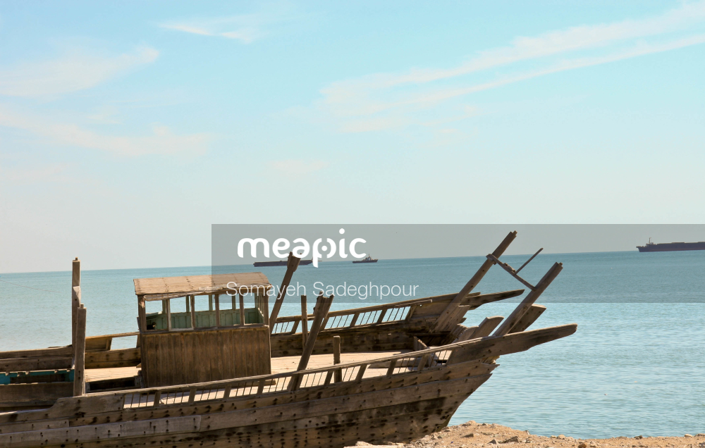 Boat Sitting On Top Of A Sandy Beach Next To The Ocean Stock Photo · Meapic