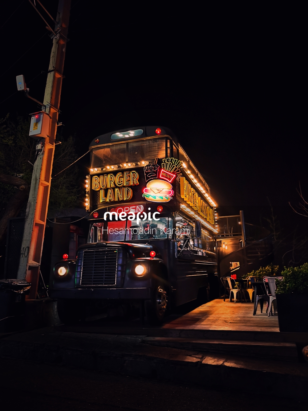 Bus Driving Down A City Street At Night Stock Photo · Meapic
