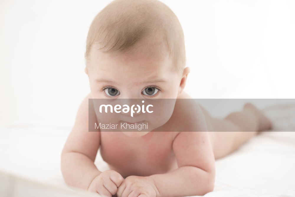 Baby Sitting On A Bed Stock Photo · Meapic