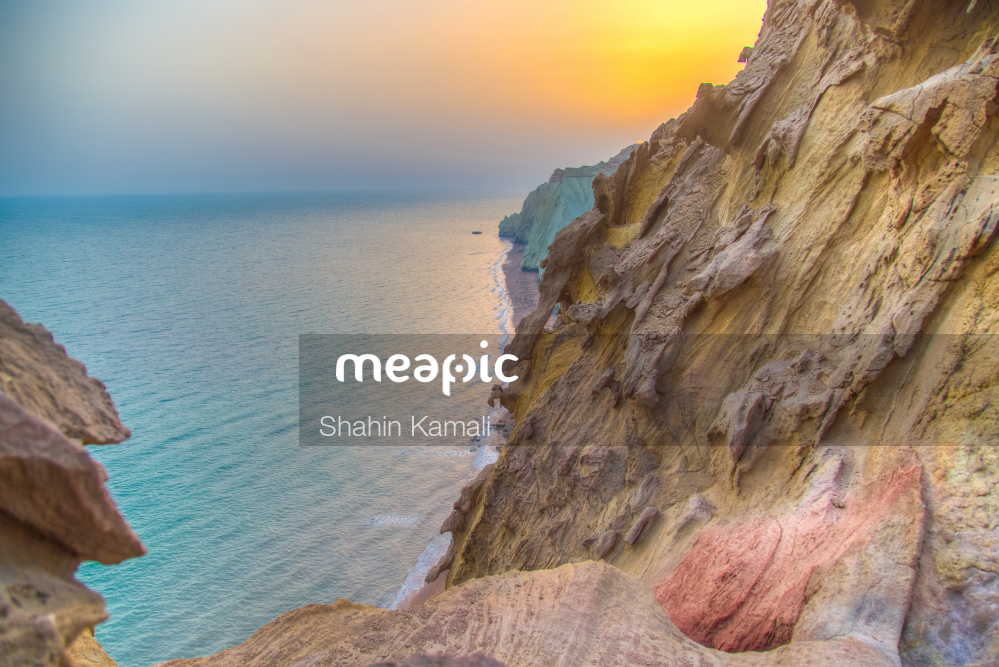 Person Sitting On A Rock Near The Ocean Stock Photo · Meapic