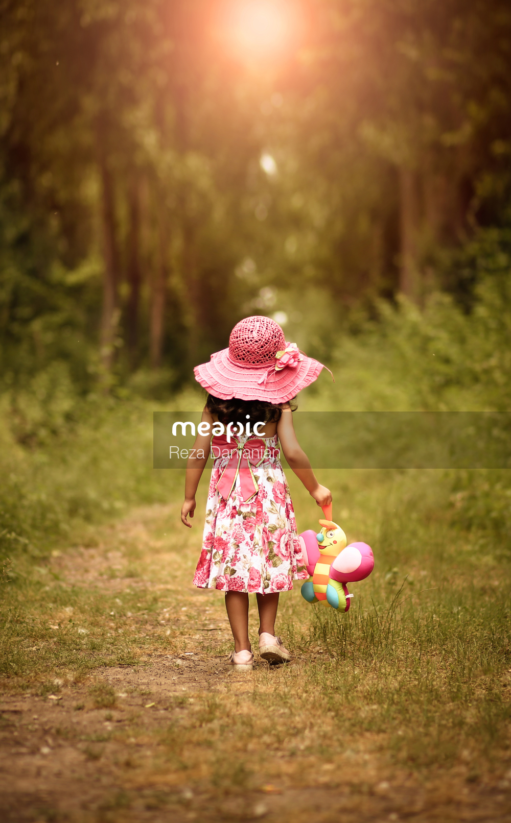 Little Girl That Is Standing In The Grass Stock Photo · Meapic