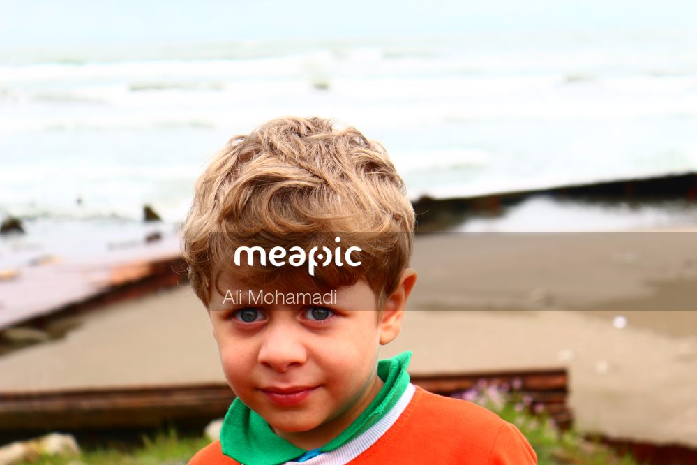 Young Boy Sitting At A Beach Stock Photo · Meapic